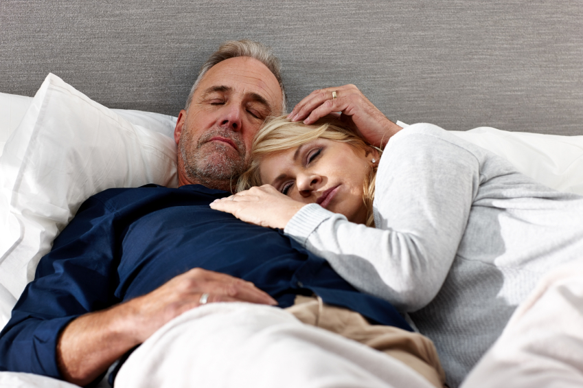 Man and woman sleep in bed