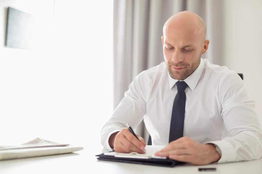 Mid adult businessman writing on clipboard in home office, bald