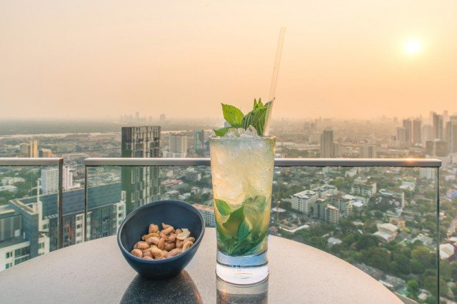 Mojito cocktail next ot a bowl of nuts on a table with the city in the background