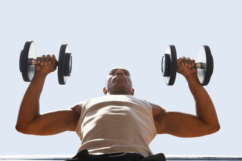 man lifting dumbbells to get rid of beer belly