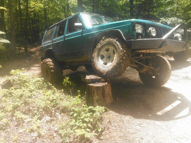 An aqua-colored Jeep Cherokee drives down some trails in the forest