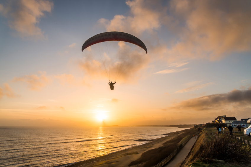 Paraglider flying over beach