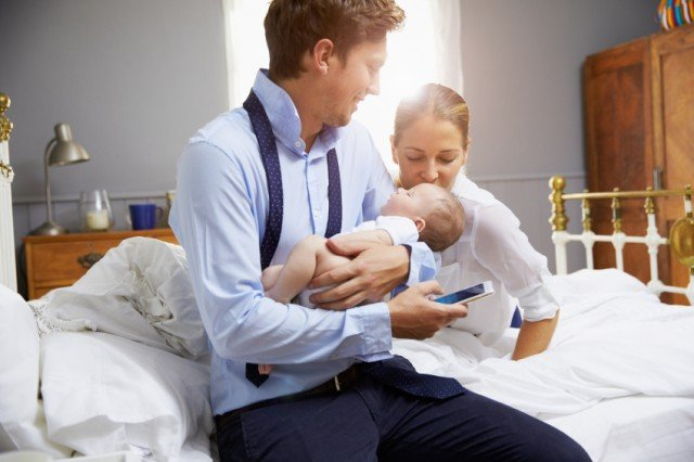 Parents With Young Baby Dressing For Work In Bedroom, dad
