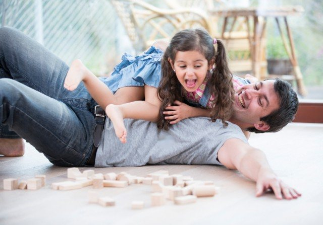 Playful daughters on top of father at home, parents, family