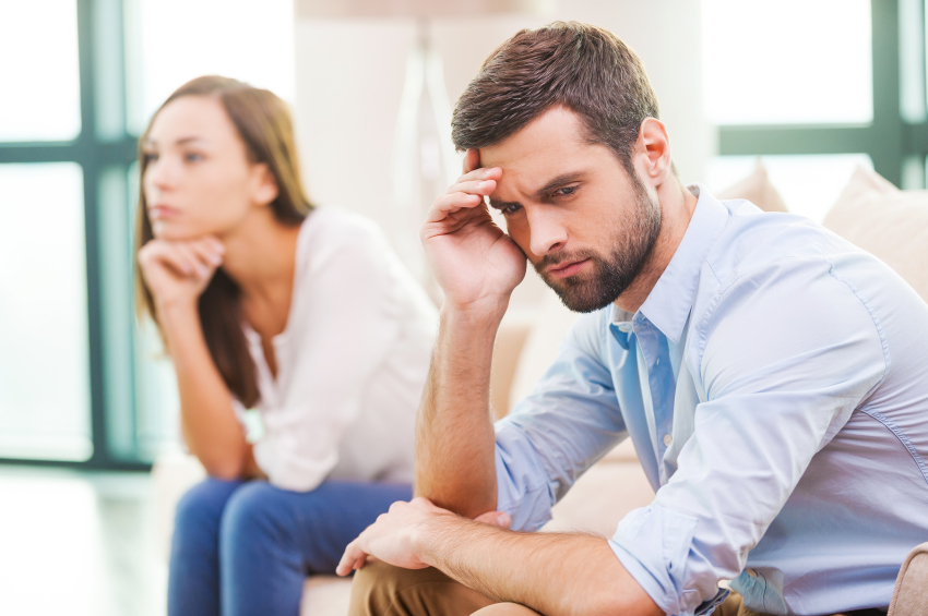 man and woman sitting next to each other looking upset