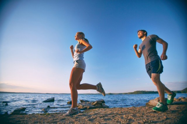 Couple running along hte beach | Source: iStock