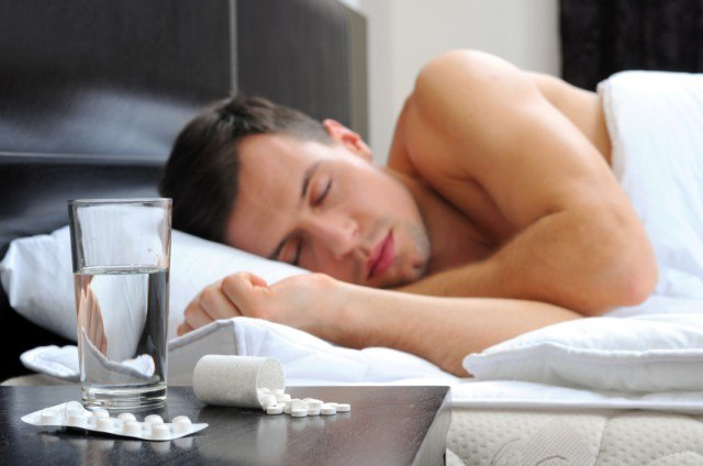 A man sleeps with a glass of water and pills on his desk side table.