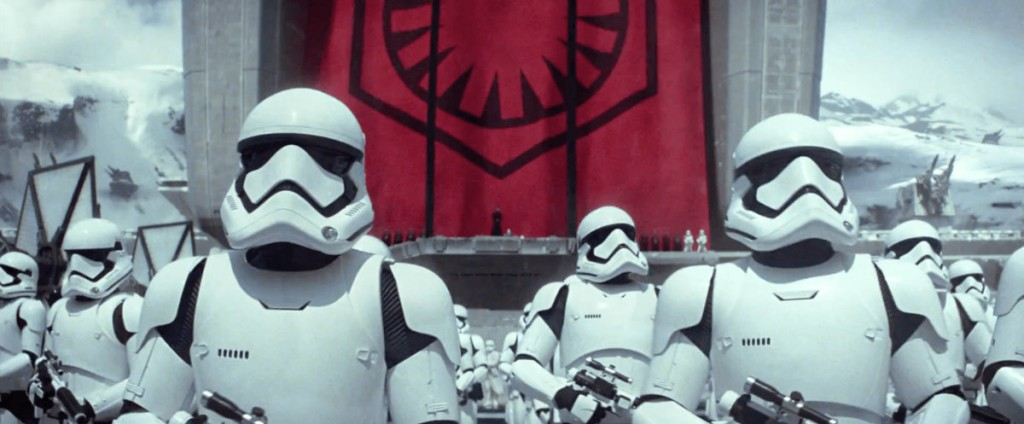 Stormtroopers looking off into the distance, in front of a red banner bearing their logo