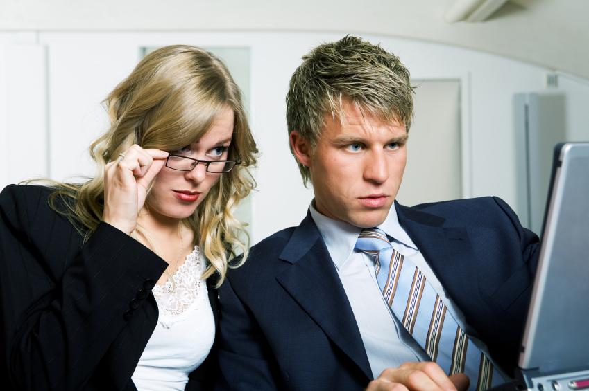man and woman looking at computer