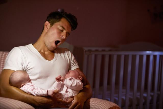 father yawning and holding two newborns
