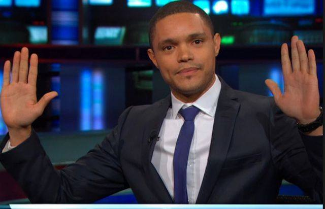 Trevor Noah with his hands up.