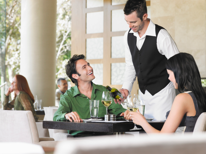 waiter serving wine to couple