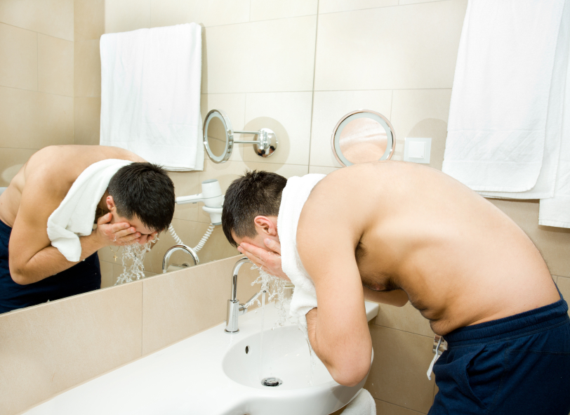 washing his face in the bathroom