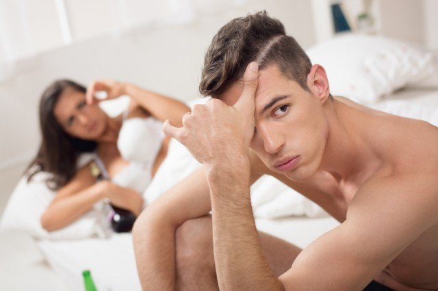 upset man looking away from his girlfriend in bed