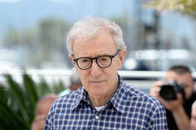 Woody Allen stands in front of the press wearing a flannel shirt and dark glasses.
