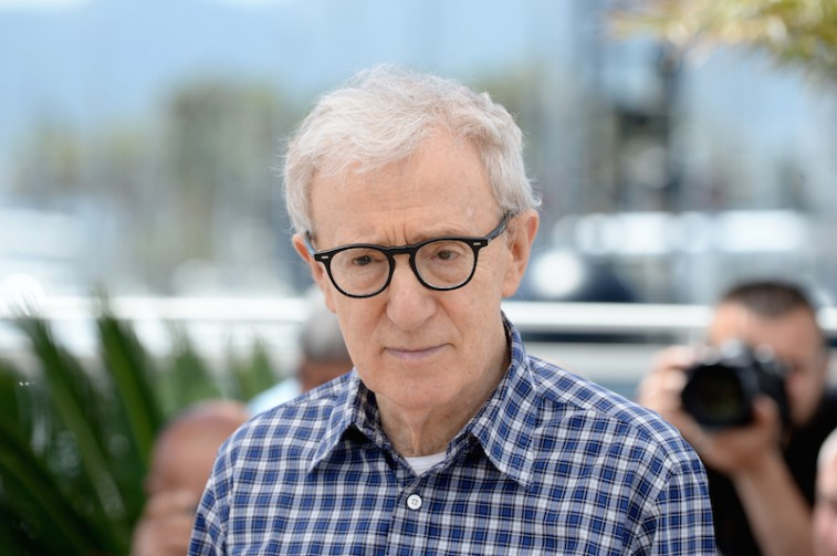 Woody Allen is wearing glasses and a flannel shirt.