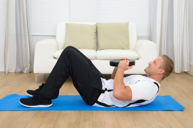 man doing sit-ups in his house