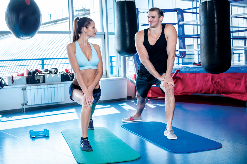 Young couple athletes athletes engaged in stretching in the gym