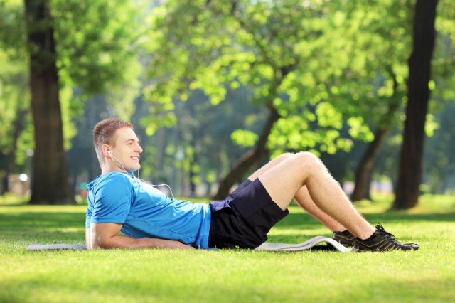 A young man lies down on fresh grass while listening to music.