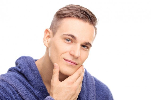 Young man checking the skin on his face, shaving, grooming