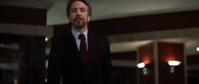 Alan Rickman as Hans Gruber in a suit standing in front of a building in Die Hard