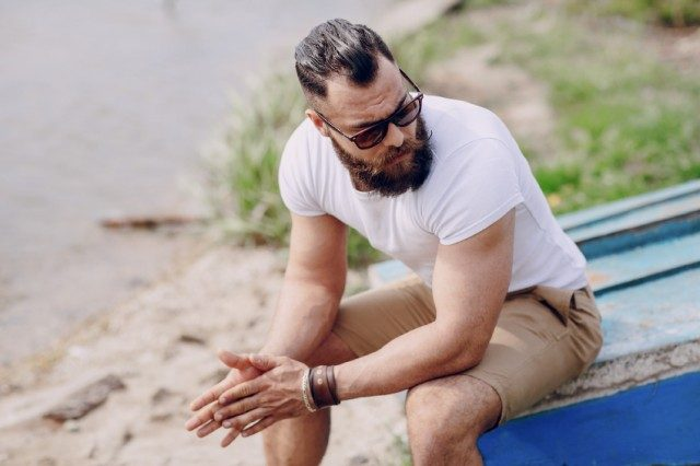 bearded man wearing sunglasses as he sits at the beach