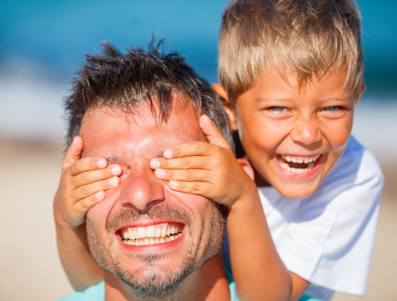 boy with father playing at the beach and laughing