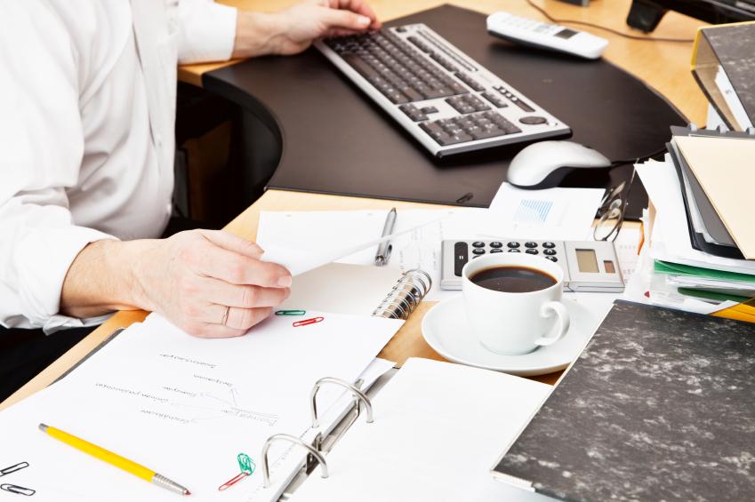 Paperwork with complex terminology litter a man's desk