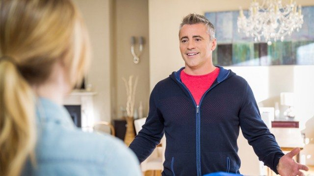 Matt LeBlanc holds up his hands while talking to a woman in Episodes