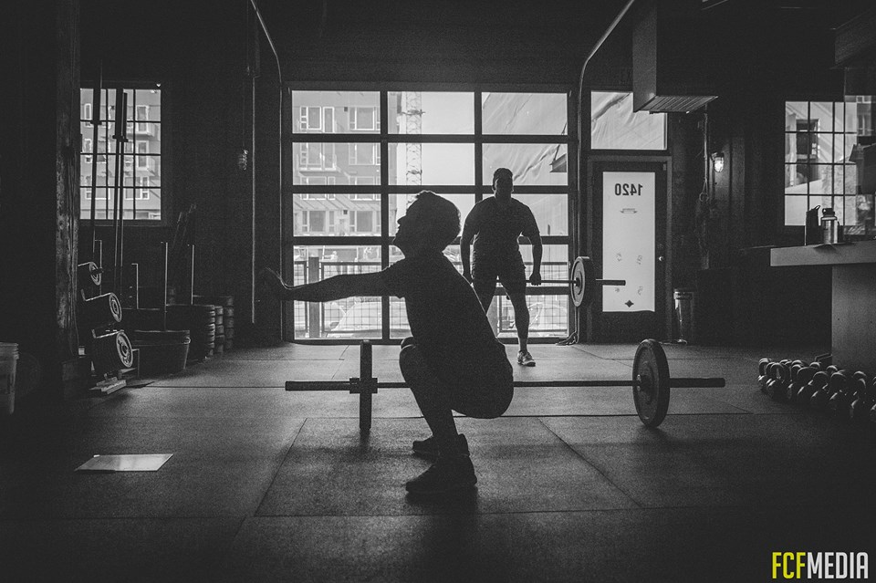 man squatting at a crossfit gym