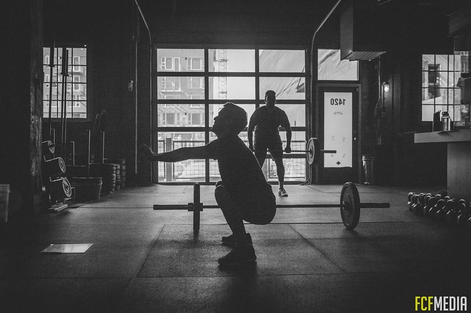 man squatting at a crossfit gym