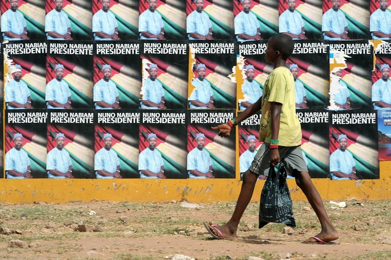 A boy passes by electoral posters in the Republic of Guinea-Bissau