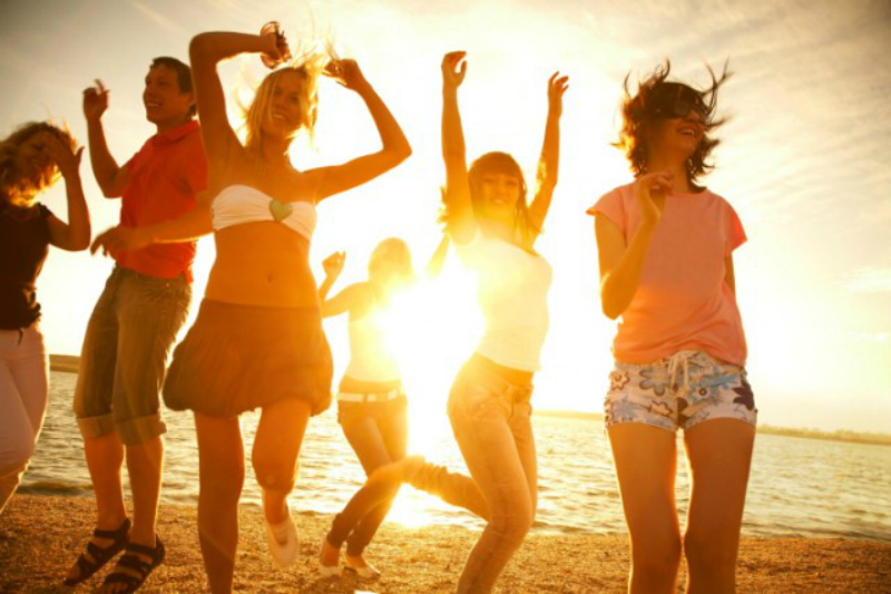 Young people dance on a beach