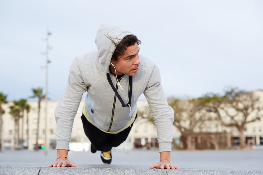 Cross-training at early morning outdoors, young man doing push ups looking away, workout, exercise