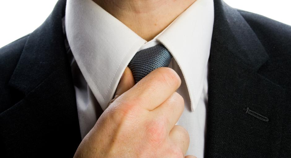 man straightening tie