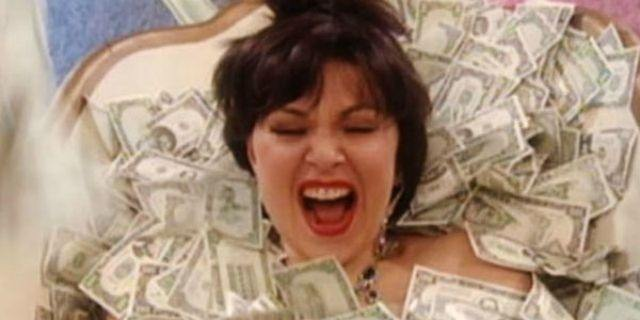 Roseanne is in a tub full of money.