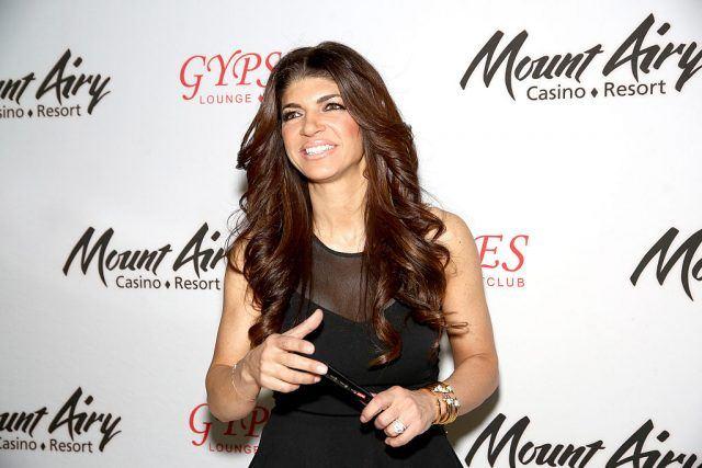 Teresa Giudice holding a pen in her hand while standing at a red carpet.