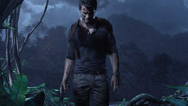 Nathan Drake stands with gun in hand in a jungle.