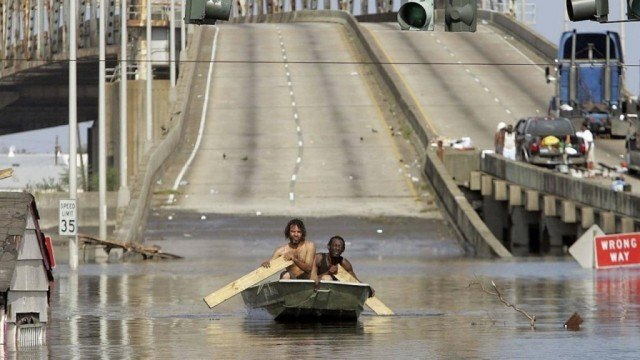 A scene from Spike Lee's documentary 'When the Levees Broke' shows two men paddling a boat away from a bridge in New Orleans