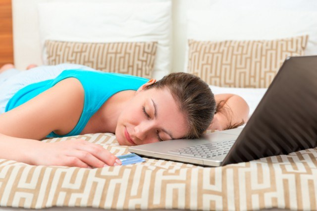 tired woman sleeping on bed with laptop