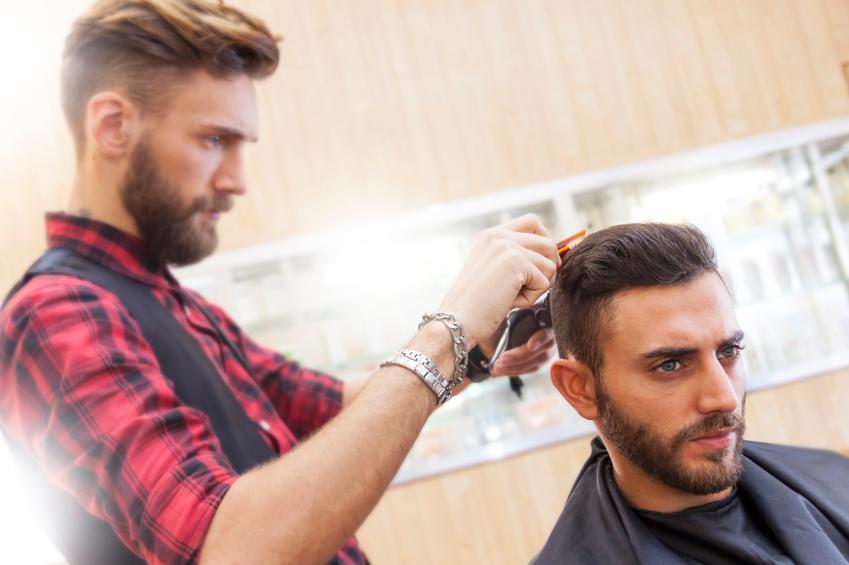 a barber cuts a man's hair