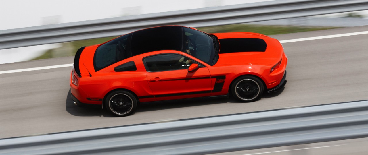 A red Ford Mustang Boss 302 speeds down the highway