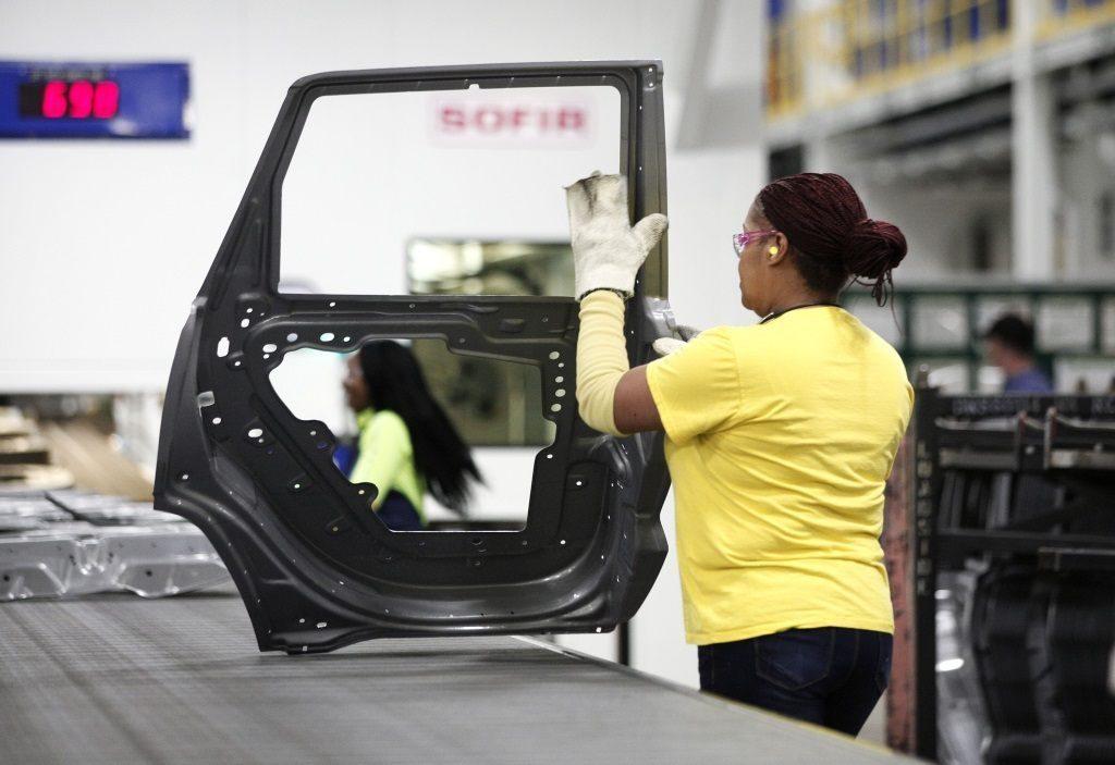 A worker handles a car door