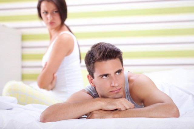 Unhappy couple sitting on a bed