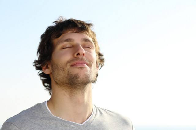 man breathing deeply outside