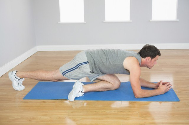 A man works out on a blue mat.