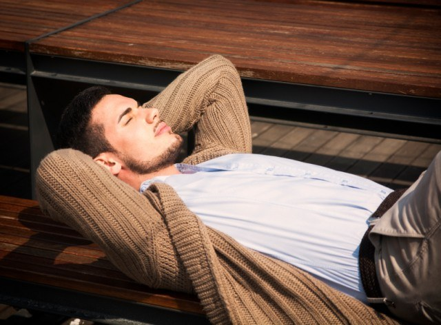 a man with a chinstrap beard laying on a bench