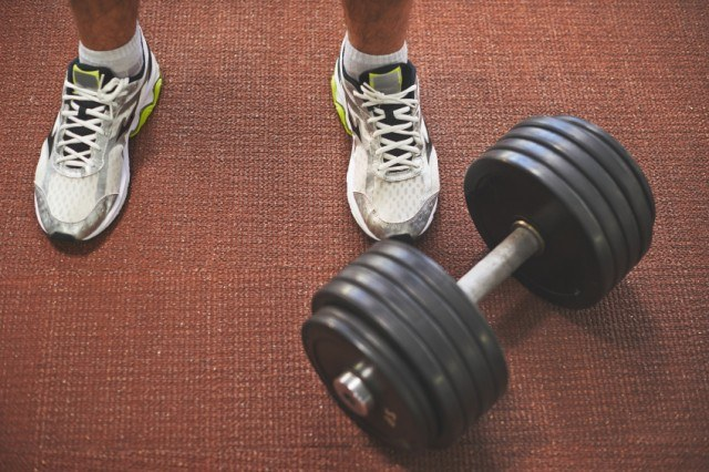Man's feet next to a dumbbell