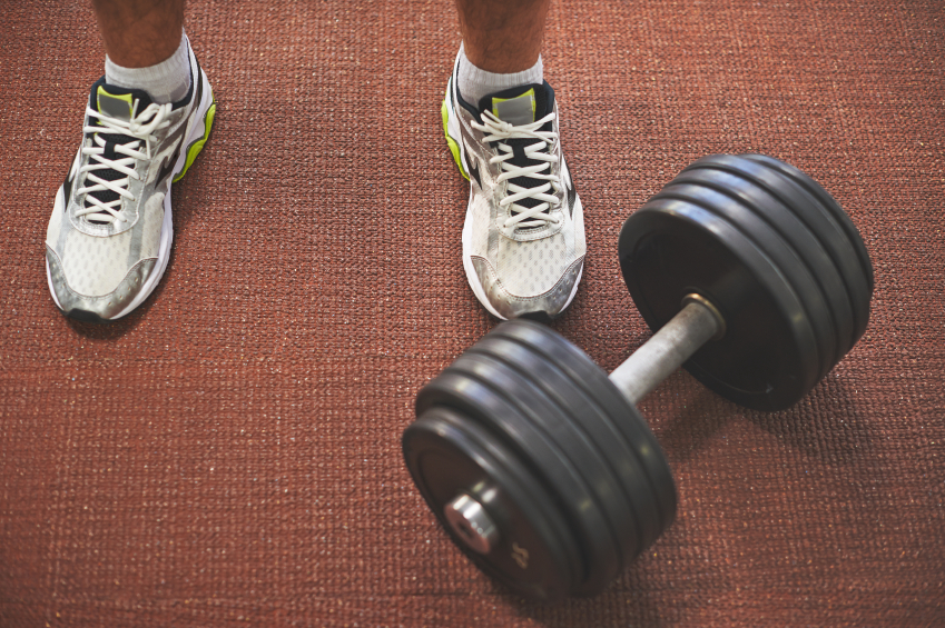 A barbell rests at a man's feet