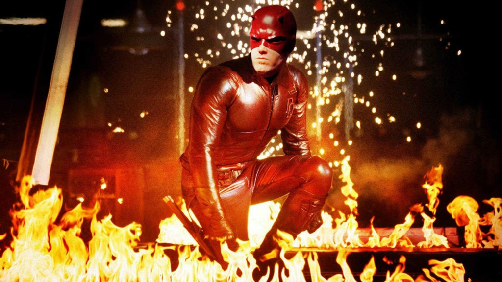 Ben Affleck as Matt Murdock in Daredevil, crouching wearing a red suit surrounded by flames